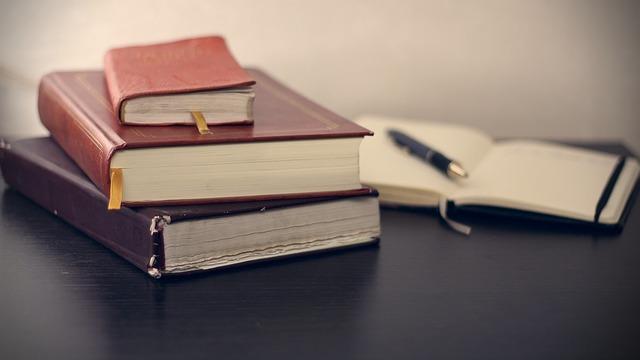 poznámkový blok za knihami